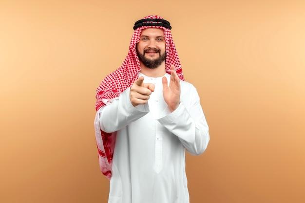 Empresário árabe masculino com roupas nacionais, apontando para a frente. copie o espaço.