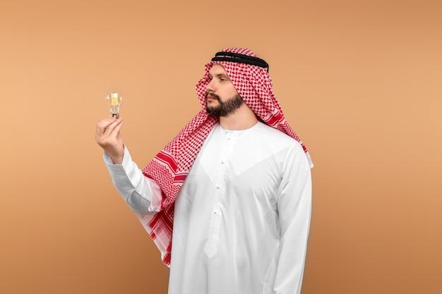 Empresário árabe masculino com roupas nacionais tem uma lâmpada incandescente nas mãos.