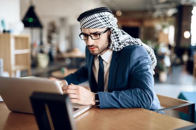 Empresário árabe no lapton na mesa no quarto de hotel