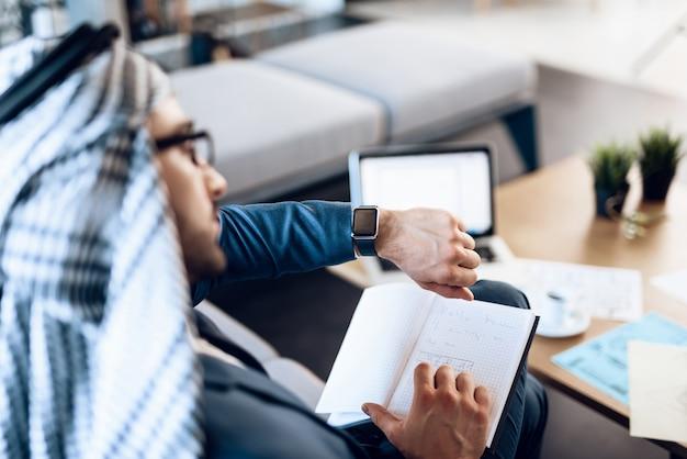 Empresário árabe tomando notas no sofá na sala de escritório