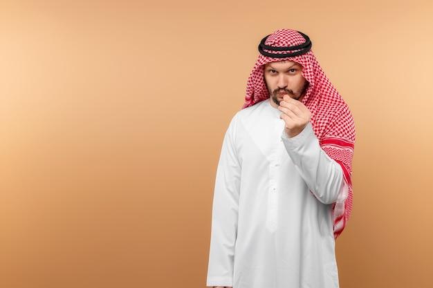 Empresário árabe vestido nacional faz gesto de dinheiro, parede bege.