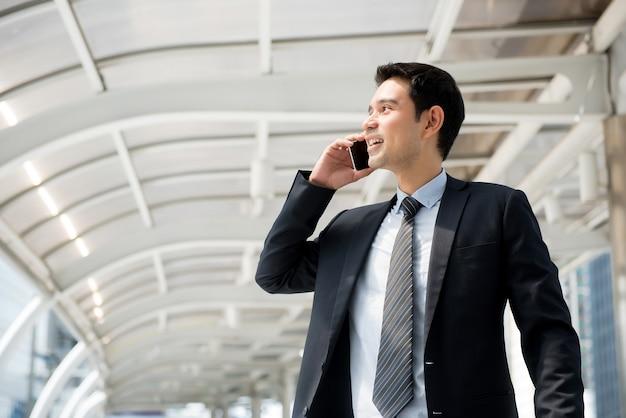 Empresário asiático bonito chamando em smartphone enquanto caminhava na cidade