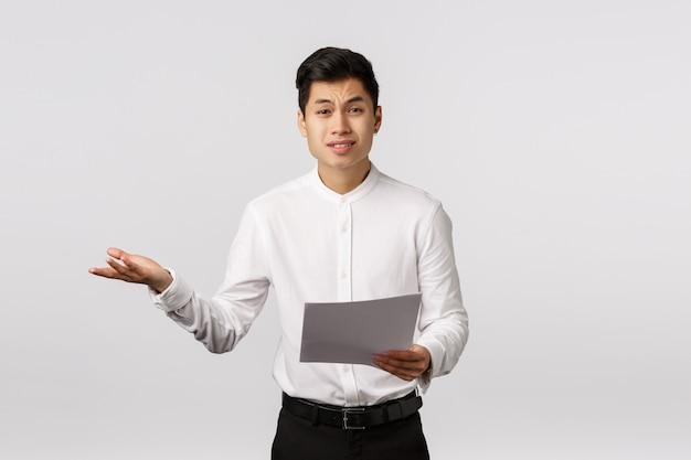 Empresário asiático cético e descontente, queixando-se insatisfeito com os documentos recebidos, encolher os ombros estende a mão para o lado, consternado, chateado, conversando com os funcionários