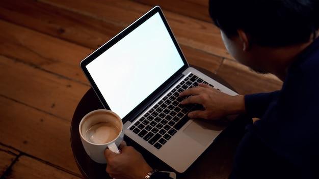 Empresário asiático com roupas casuais, bebendo café e trabalhando com tela branca lapto