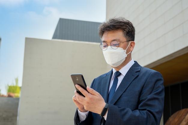 Empresário asiático de meia idade na cidade usando uma máscara e um smartphone.