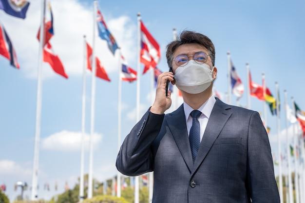 Empresário asiático de meia-idade usando uma máscara e um smartphone sob várias bandeiras nacionais tremulando ao vento.