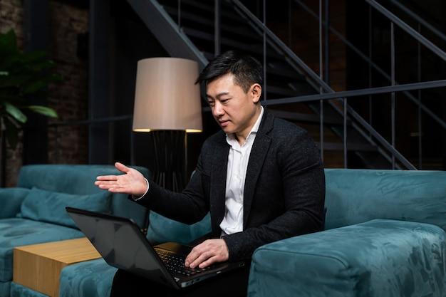 Empresário asiático de sucesso em um terno preto trabalhando em um laptop relaxando em um restaurante