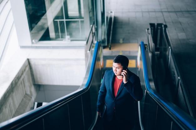 Empresário asiático de terno e subindo uma escada rolante em uma estação de metrô durante seu trajeto de manhã