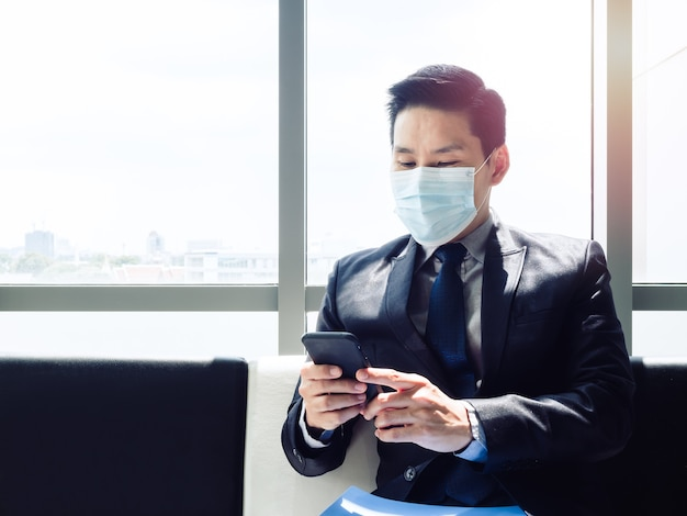 Empresário asiático de terno usando máscara protetora e smartphone enquanto está sentado em um prédio de escritórios moderno perto de uma enorme janela de vidro