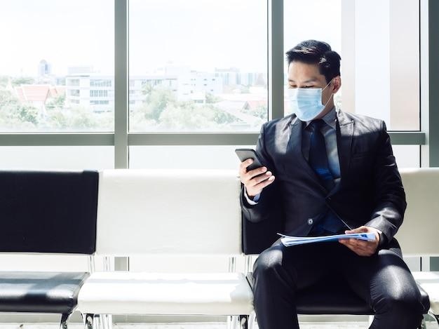 Empresário asiático de terno usando máscara protetora usando telefone celular enquanto está sentado em um prédio de escritórios moderno perto de uma enorme janela de vidro.
