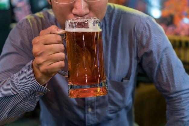 Empresário asiático em ação de felicidade e bebendo cerveja depois do trabalho ou trabalho de sucesso