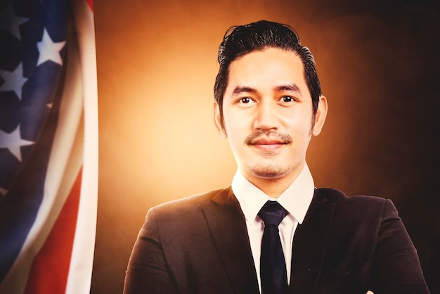 Empresário asiático em pé com uma bandeira americana, com uma vista brilhante. conceito de quatro de julho