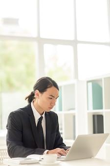 Empresário asiático embrulhado no trabalho