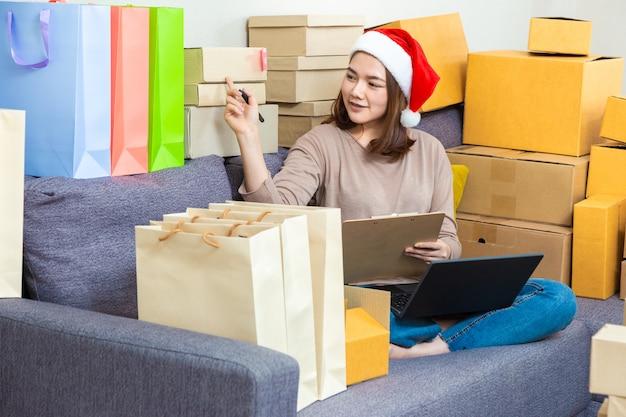 Empresário asiático jovem feminino vendedor on-line, usando chapéu de natal, trabalhando em seu negócio on-line