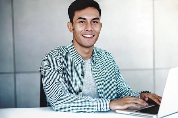 Empresário asiático jovem inteligente trabalhando no computador portátil no escritório