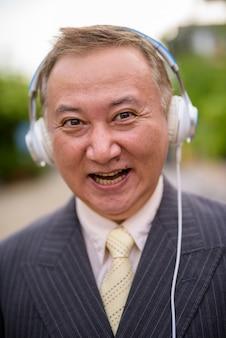 Empresário asiático maduro ouvindo música nas ruas supera