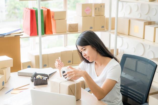 Empresário asiático mulheres trabalhando em casa com a caixa de embalagem no local de trabalho