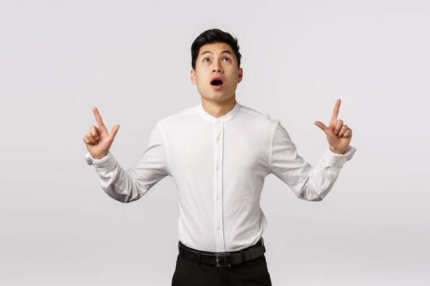 Empresário asiático preocupado, chocado e assustado, vê algo caindo do céu, boca aberta ofegando, tremendo e emocionado, apontando para cima, olhando sem fala e espantado,