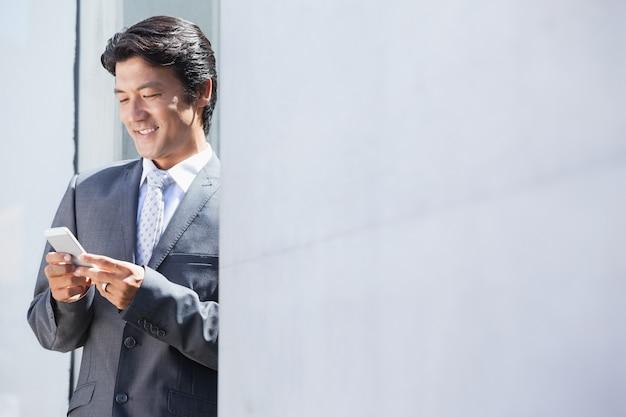 Empresário asiático que envia mensagem de texto