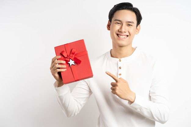 Empresário asiático segurando uma caixa de presente vermelha sobre fundo branco