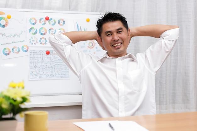 Empresário asiático sentado no escritório em casa olha para a câmera, fazendo uma entrevista de trabalho online durante o bate-papo da videoconferência.