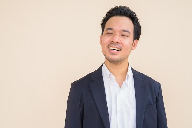 Empresário asiático sorrindo e relaxando com os olhos fechados