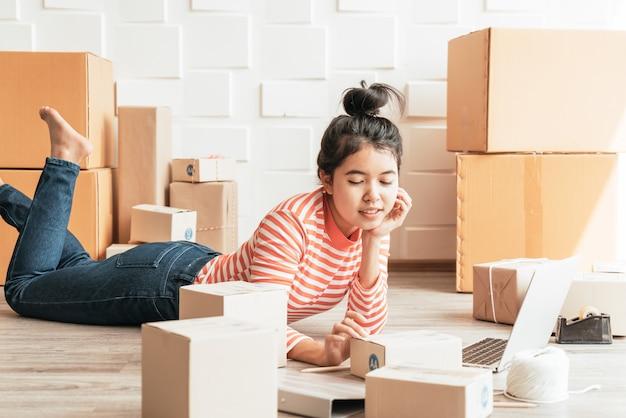 Empresário asiático trabalhando em casa com a caixa de embalagem no local de trabalho