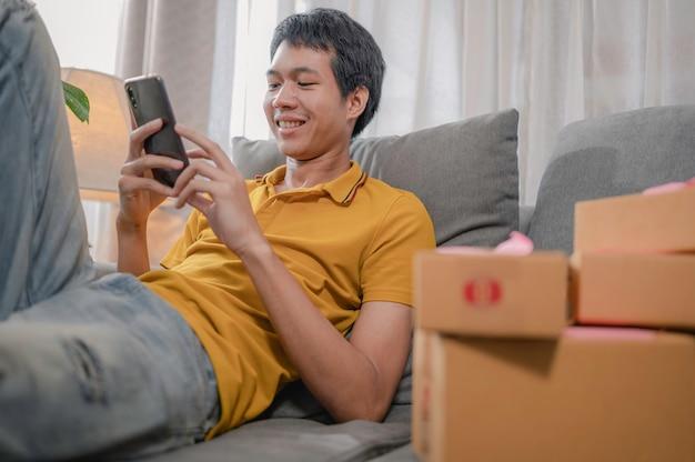 Empresário asiático trabalhando em casa. ele sorria alegremente enquanto respondia às mensagens
