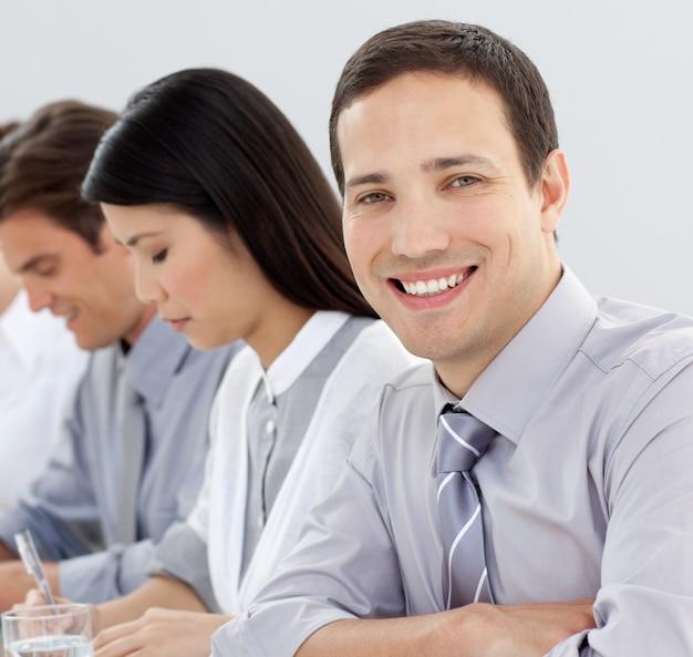 Empresário atraente em uma conferência com seu time
