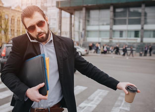 Empresário barbudo com uma xícara de café, pegar um táxi. ele não tem tempo, vai falar ao telefone em qualquer lugar. homem fazendo várias tarefas. homem de negócios multitarefa persone.