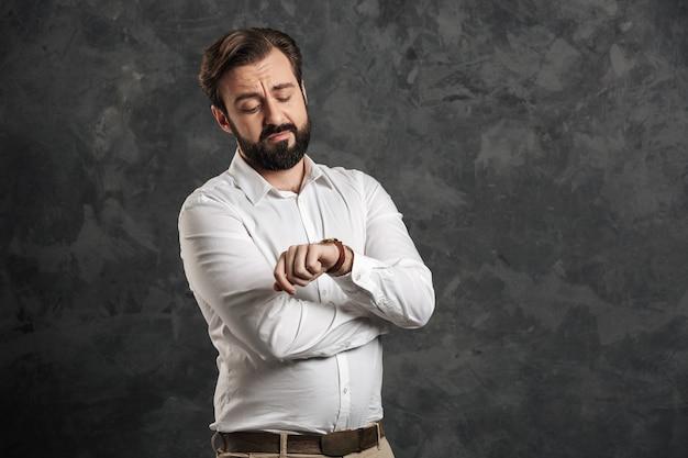 Empresário barbudo concentrado, olhando para o relógio.
