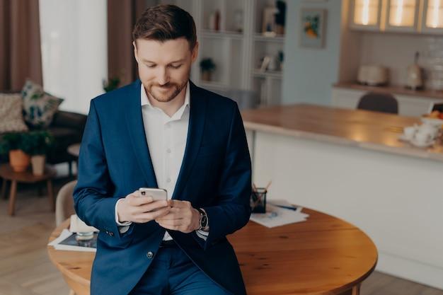 Empresário barbudo confiante em um terno elegante, encostado na mesa da sala e lendo mensagens ou últimas notícias na internet enquanto segura o smartphone. conceito de estilo de vida de empresários