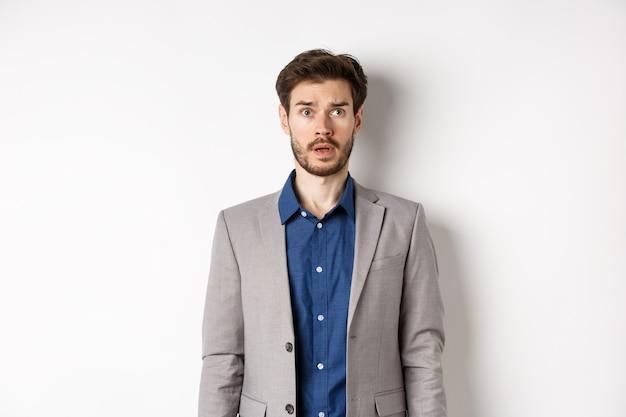 Empresário barbudo confuso em terno olhando para o logotipo do canto superior direito em causa, nervoso sobre fundo branco.
