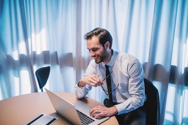 Empresário barbudo elegante caucasiano ambicioso de camisa e gravata segurando óculos e usando o laptop enquanto está sentado no escritório.