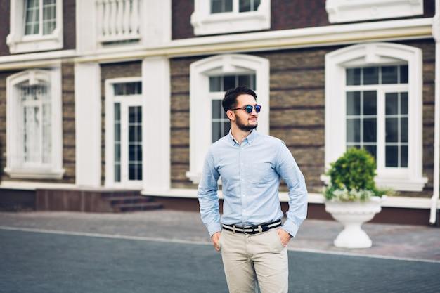 Empresário barbudo em óculos de sol, andando na rua. ele segura as mãos nos bolsos, sorrindo ao longe.
