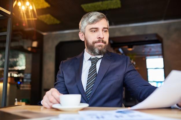 Empresário barbudo em trajes formais elegantes, tomando uma xícara de chá e olhando através de contrato antes da consulta com o cliente