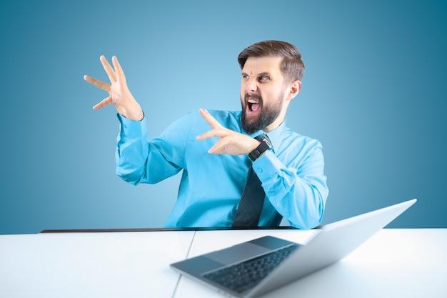 Empresário barbudo no computador abriu a boca e gesticulou com as mãos para o lado