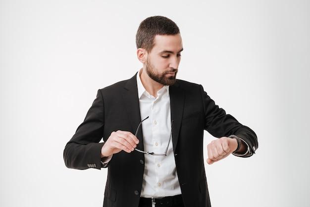 Empresário barbudo olhando para o relógio.
