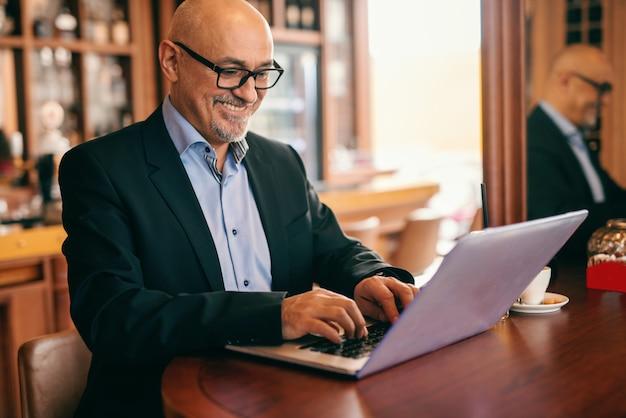 Empresário barbudo sênior em terno usando laptop para o trabalho enquanto está sentado na lanchonete.
