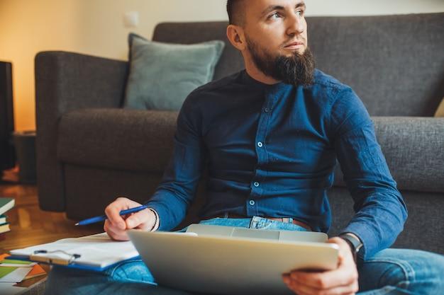 Empresário barbudo trabalhando no chão em frente ao computador com alguns documentos e olhando para o outro lado pensando em algo