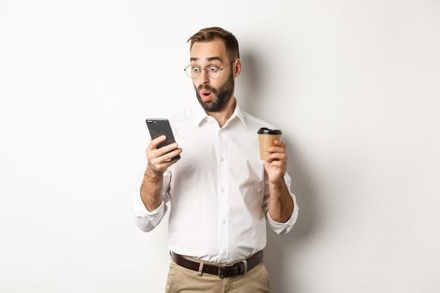 Empresário bebendo café e parecendo surpreso com a mensagem no celular, parado espantado com o fundo branco.