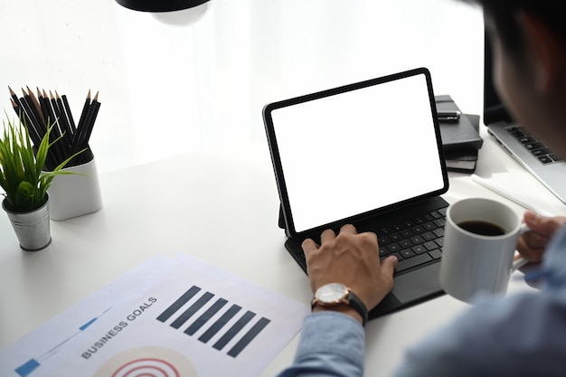 Empresário, bebendo café e trabalhando em um tablet na mesa do escritório.
