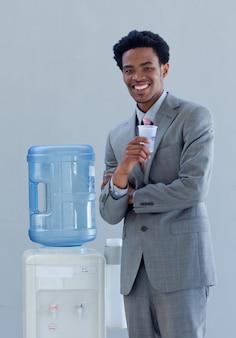 Empresário bebendo de um aquecedor de água no escritório