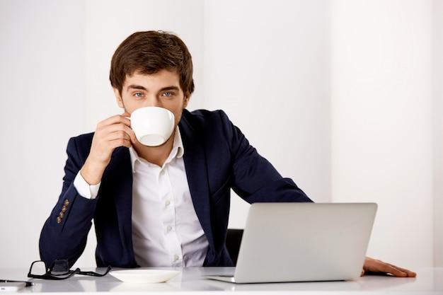 Empresário bem sucedido bonito de terno, sente seu escritório com laptop, bebendo café, pronto trabalho produtivo