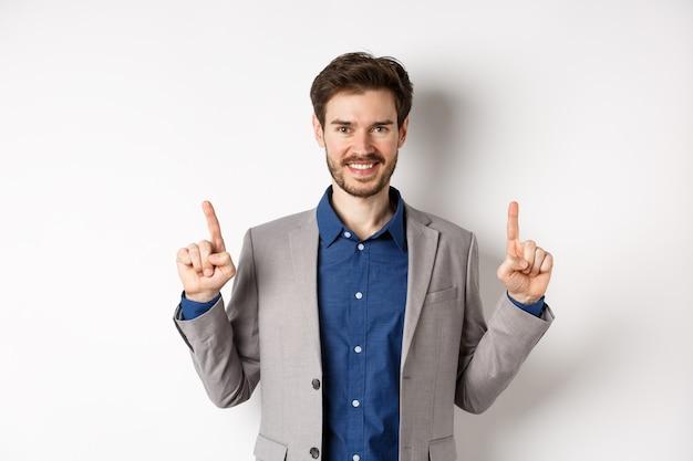Empresário bem sucedido confiante apontando os dedos para cima, sorrindo e mostrando o logotipo da empresa, de pé no terno sobre fundo branco.
