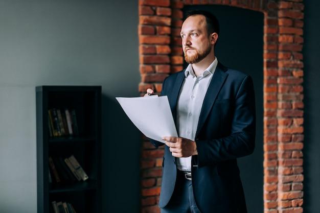 Empresário bem sucedido de terno fica e mantém um relatório financeiro em papel.
