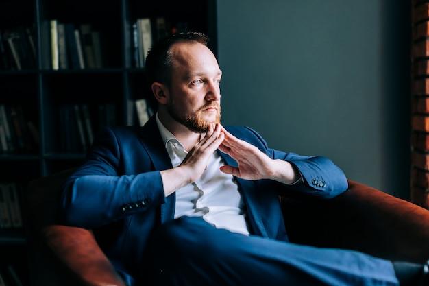 Empresário bem sucedido de terno se senta em uma cadeira com braços cruzados e olha pela janela.