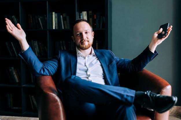 Empresário bem sucedido de terno se senta em uma cadeira de um escritório na moda.