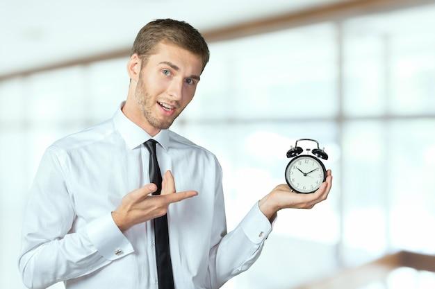 Empresário bem sucedido em roupa formal, apontando para o relógio