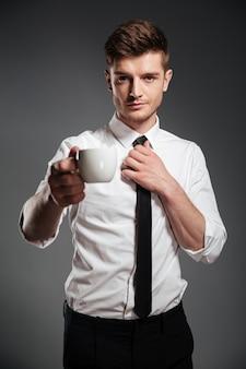 Empresário bem sucedido em trajes formais, segurando a xícara de café em pé